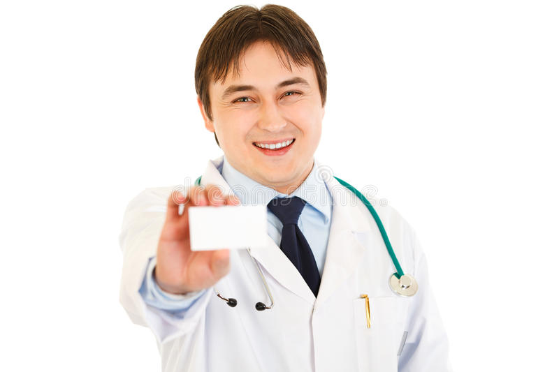 Doctor holding blank business card in hand. Smiling medical doctor holding blank business card in hand isolated on white royalty free stock photography