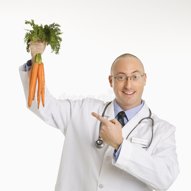 Doctor holding carrots. royalty free stock photography