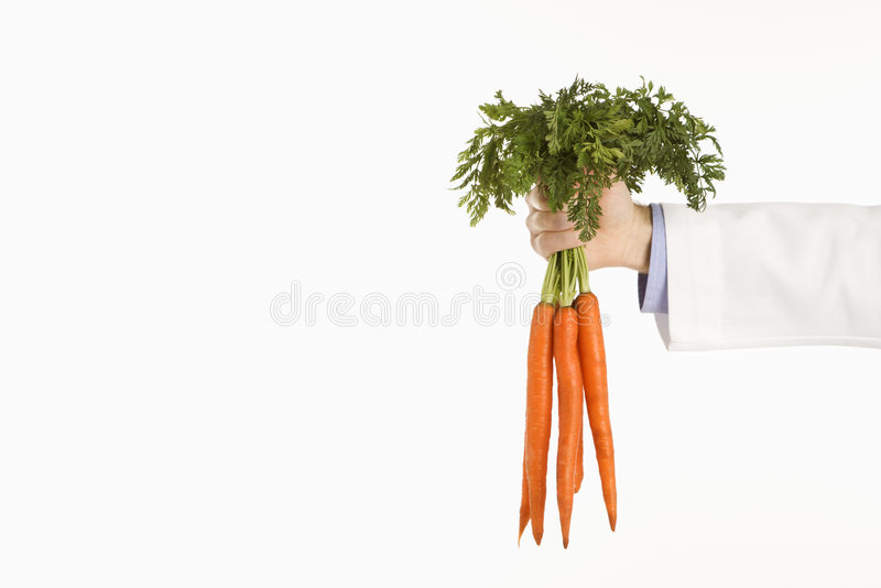 Doctor holding carrots. stock image