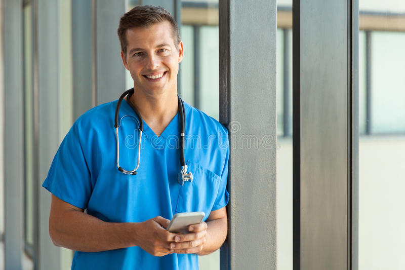 Doctor holding cell phone. Happy young doctor holding cell phone stock photography
