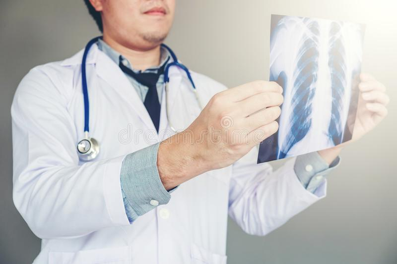 Doctor holding and checking chest x-ray film or roentgen image in ward hospital royalty free stock photo