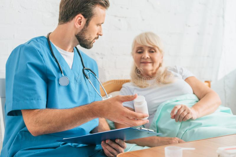 doctor holding clipboard and showing pills to senior woman stock images