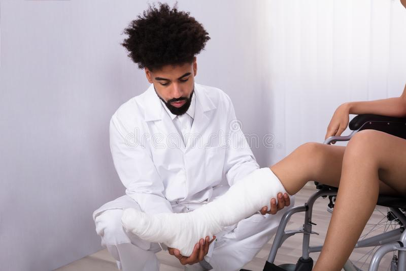 Doctor Holding Disabled Woman`s Leg royalty free stock image
