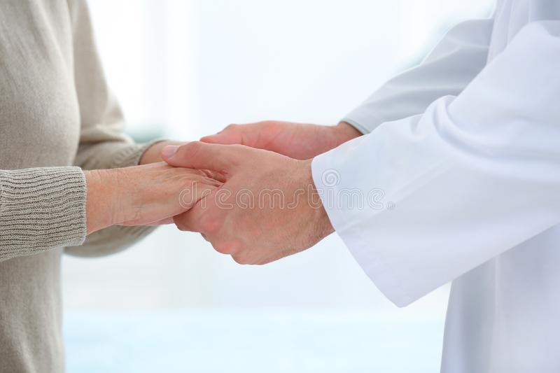 Doctor holding elderly patient hands on light background royalty free stock image