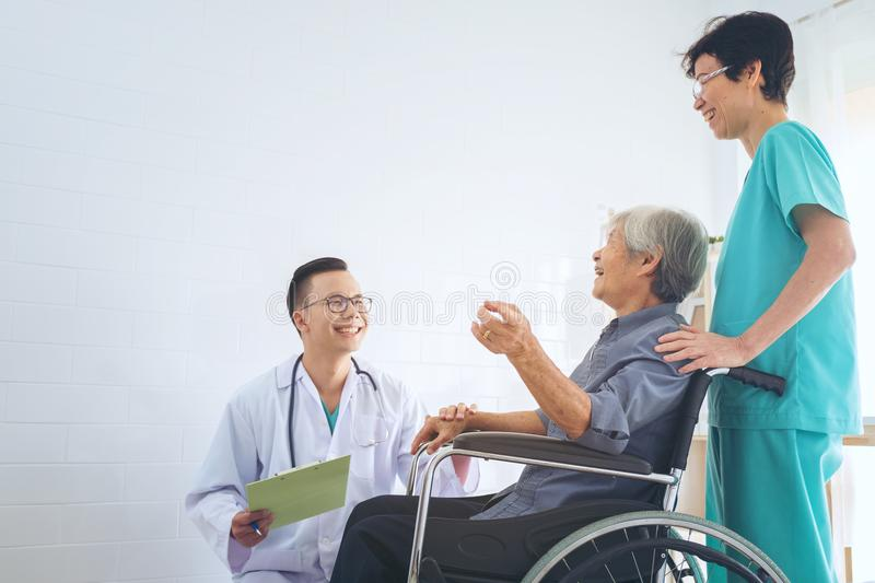Doctor holding elderly patient `s hand in a wheelchai, giving su royalty free stock photography