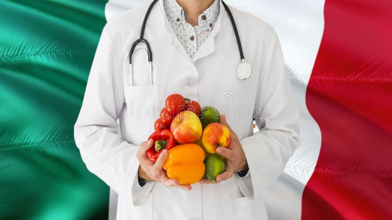 Doctor is holding fruits and vegetables in hands with Mexico flag background. National healthcare concept, medical theme stock photos