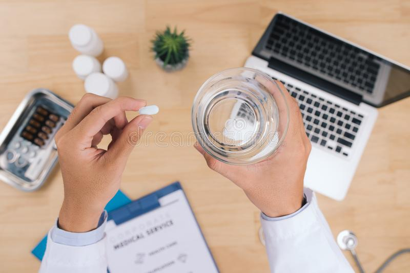 Doctor holding a glass of water and pill medicine close up. Heal stock image