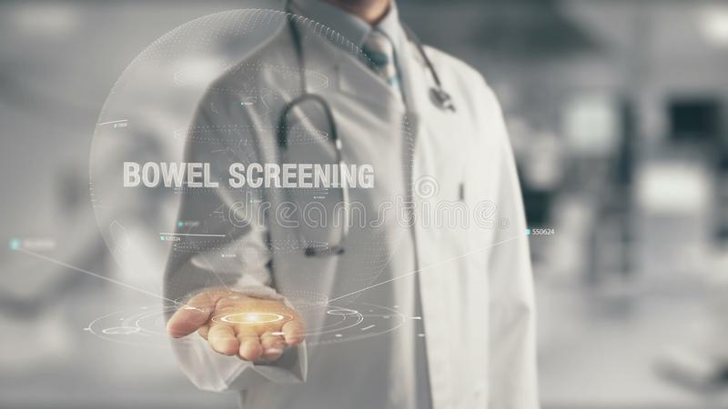 Doctor holding in hand Bowel Screening. Concept of application new technology in future medicine stock photography