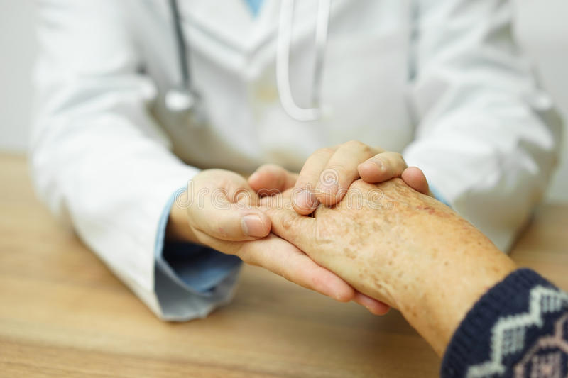 Doctor holding hand of elderly woman stock images