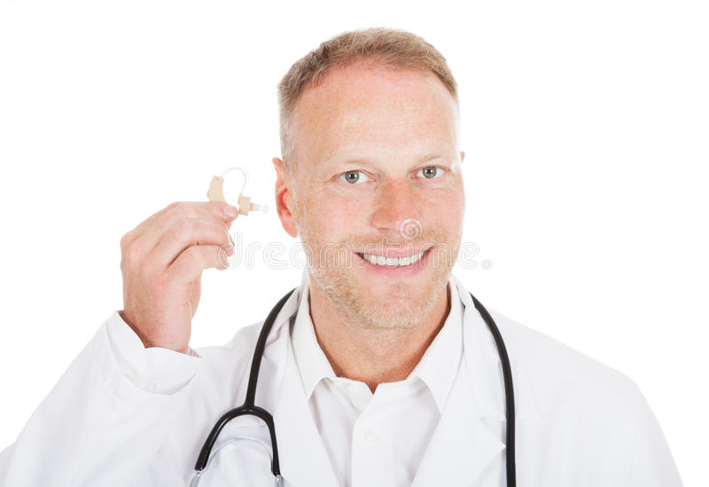 Doctor Holding Hearing Aid Device. Portrait of smiling mid adult doctor holding hearing aid device over white background royalty free stock images