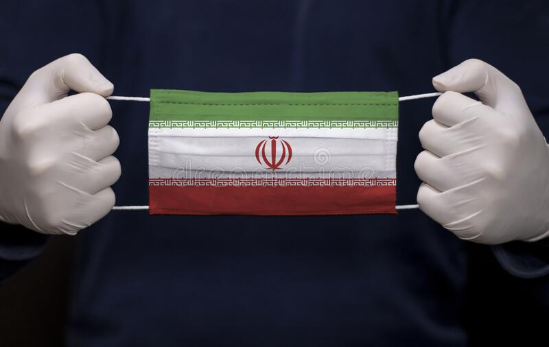 Doctor holding medical face mask with Iran flag. Health employee doctor holding medical face mask with Iran flag. Coronavirus COVID-19 pandemic affects the royalty free stock photos