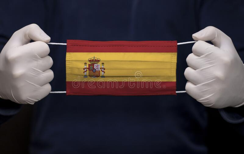 Doctor holding medical face mask with Spain flag. Health employee doctor holding medical face mask with Spain flag. Coronavirus COVID-19 pandemic affects the royalty free stock photography