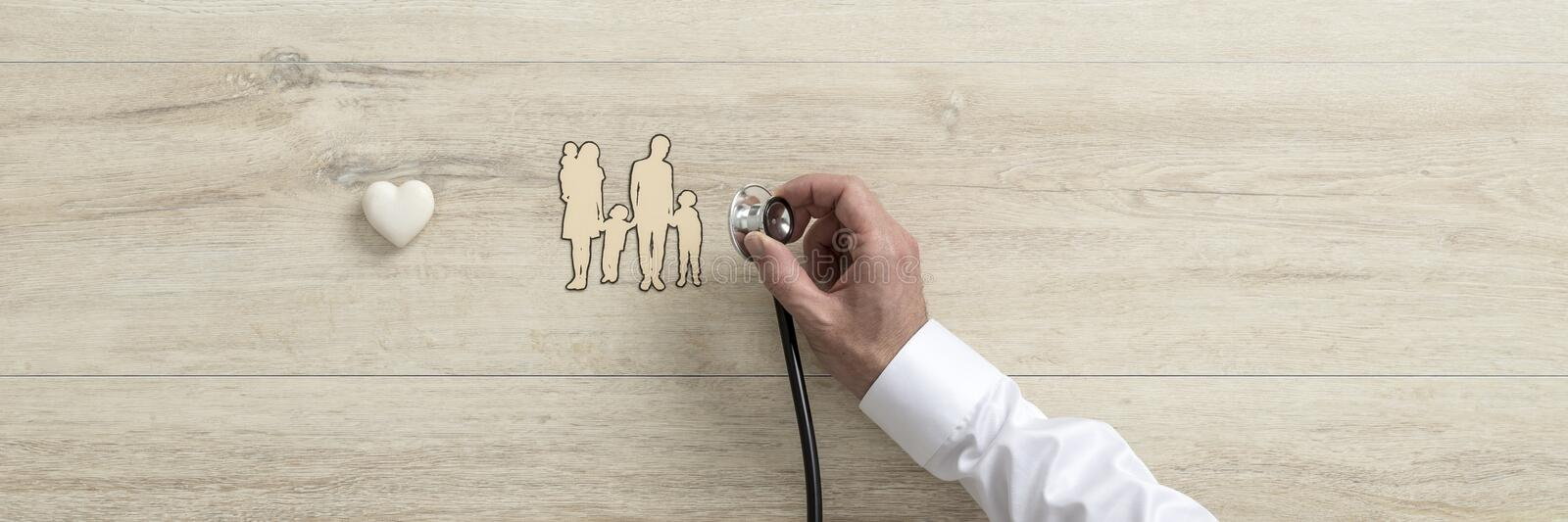 Doctor holding medical stethoscope over a cut out of a family royalty free stock image