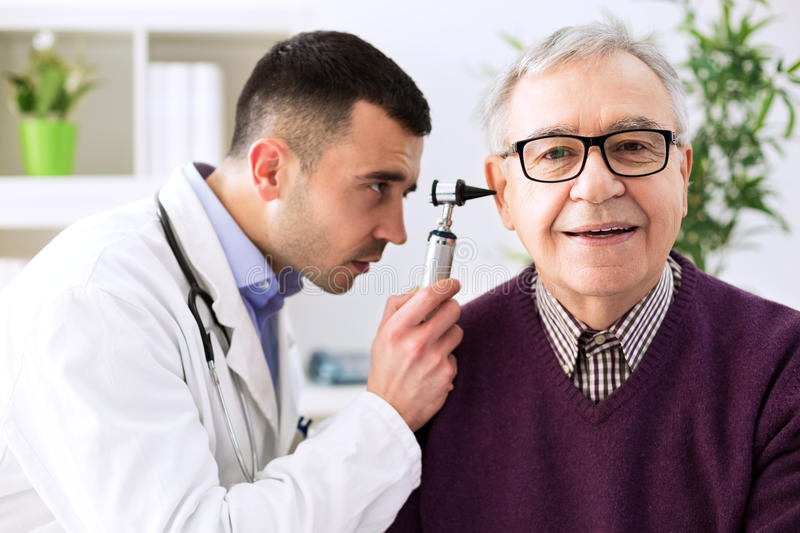 Doctor holding otoscope and examining patient ear royalty free stock photo