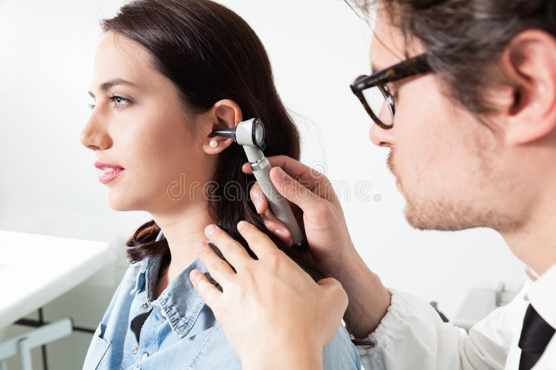 Doctor holding otoscope and Examining a woman patient ear. Otolaryngology Doctor Inspecting the ear canal and eardrum during an ENT exam royalty free stock images
