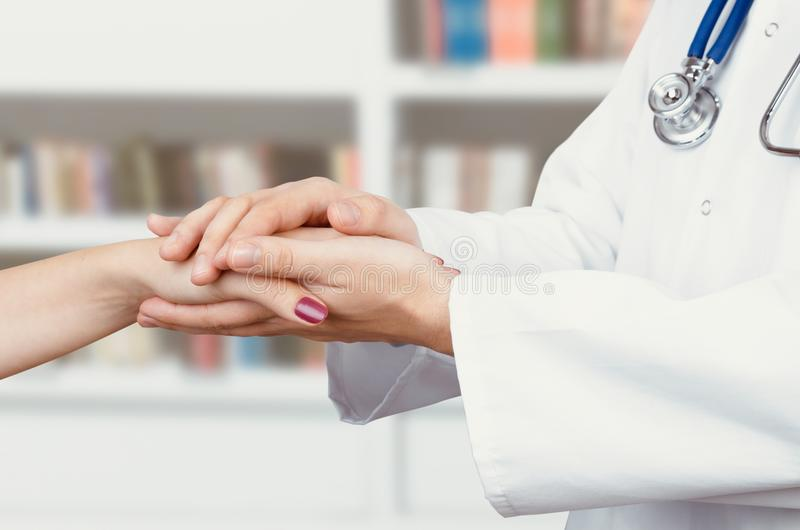 Doctor holding patient hand close up royalty free stock photo