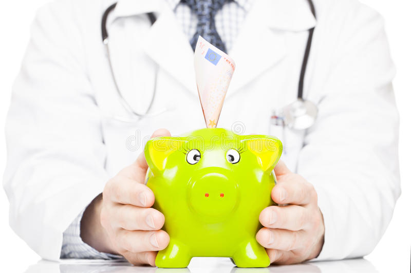 Doctor holding piggy bank as an idea of savings for medical expenses. Male doctor holding piggy bank as an idea of savings for medical expenses stock image