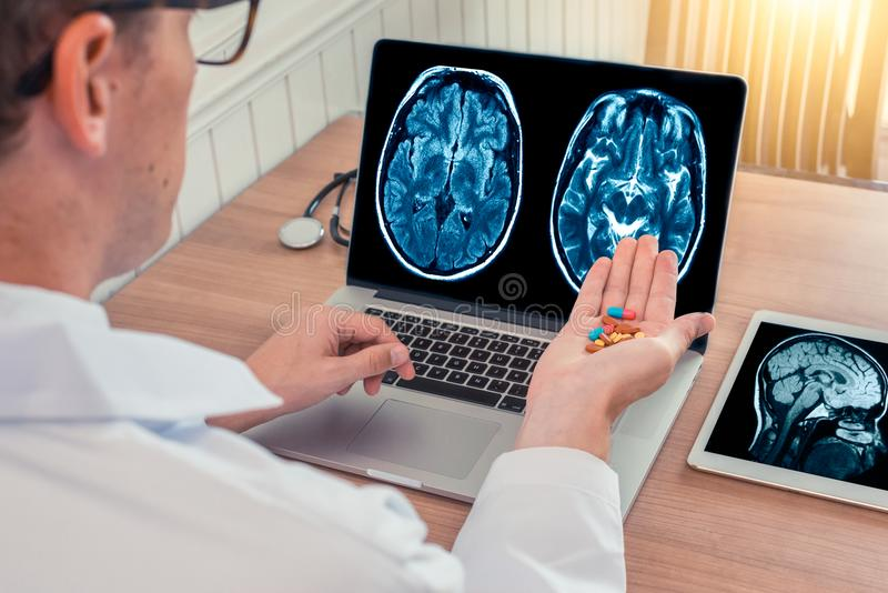 Doctor holding pills for disease with x-ray of brain and skull on the laptop. Digital tablet on the wooden desk stock image