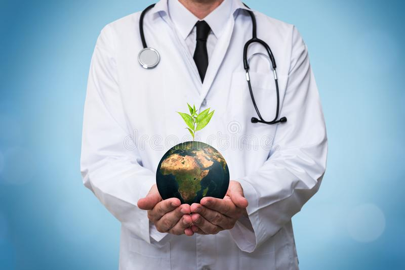 Doctor holding a planet earth globe in his hands. Environment and healthy concept for global ecology royalty free stock photo