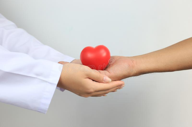 Doctor holding a red heart ball to Senior man on white background, Medicine and Health care concept royalty free stock photos