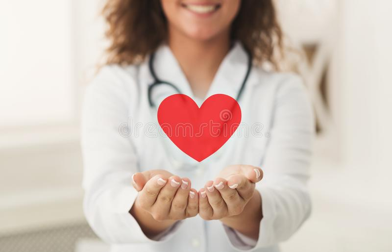 Doctor holding red heart in cupped hands. Health support. Doctor holding red heart in cupped hands royalty free stock photo