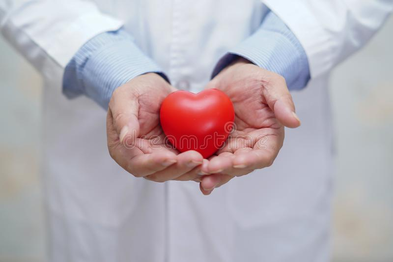 Doctor holding red heart in his hand in nursing hospital ward : healthy strong medical royalty free stock photography