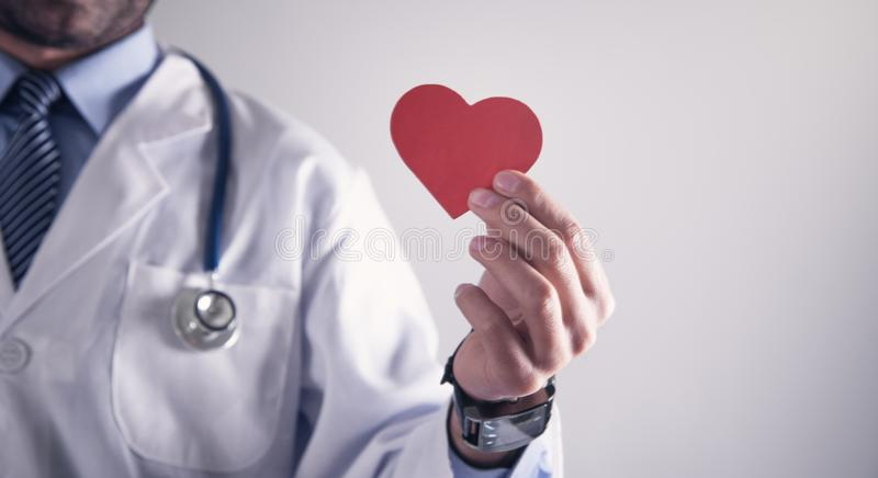 Doctor holding red paper heart. Healthcare and cardiology concept stock images