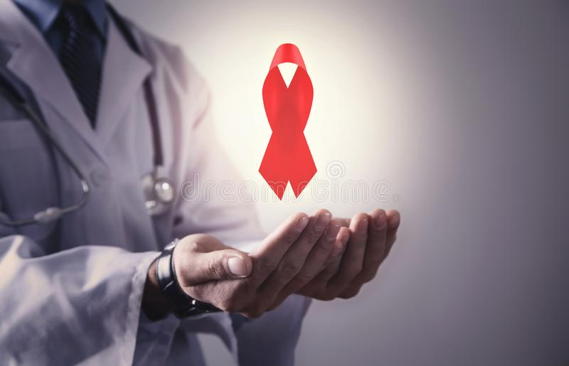 Doctor holding red ribbon. World aids day royalty free stock photos