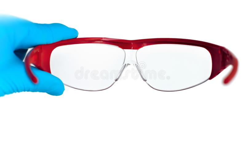 Doctor holding safety glasses in white background royalty free stock images