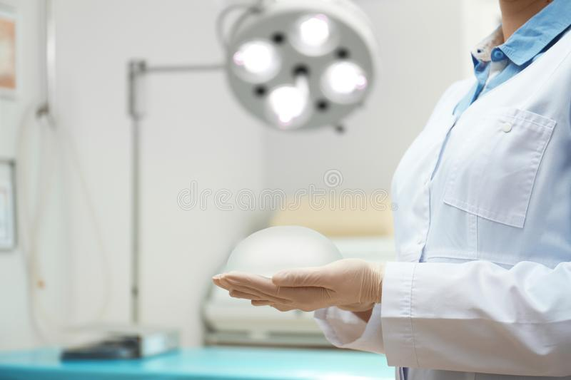 Doctor holding silicone implant for breast augmentation in clinic, closeup. With space for text. Cosmetic surgery stock image