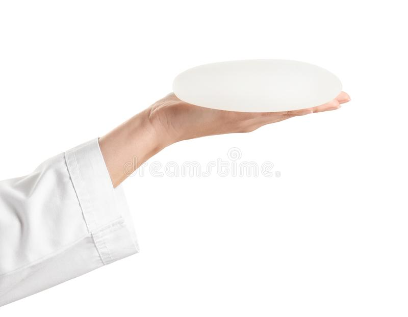 Doctor holding silicone implant for breast augmentation on white background. Cosmetic surgery royalty free stock images