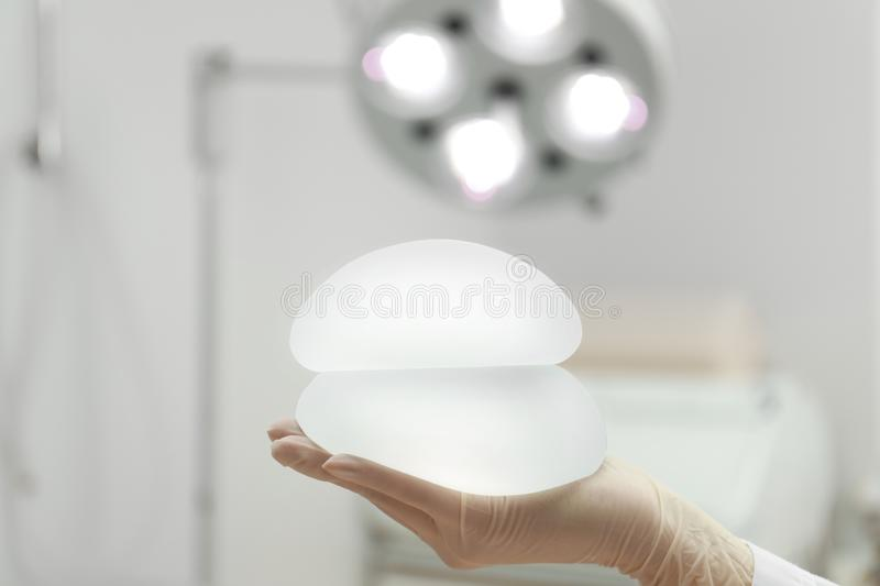 Doctor holding silicone implants for breast augmentation in clinic, space for text. Cosmetic surgery stock image