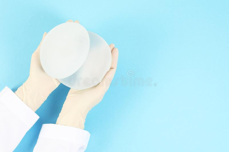 Doctor holding silicone implants for breast augmentation. Cosmetic surgery. Doctor holding silicone implants for breast augmentation on color background, top royalty free stock image
