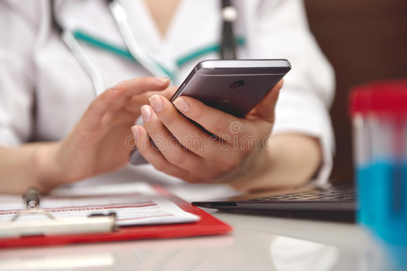 Doctor holding smart phone. Female medicine doctor holding mobile smart phone. close up royalty free stock images