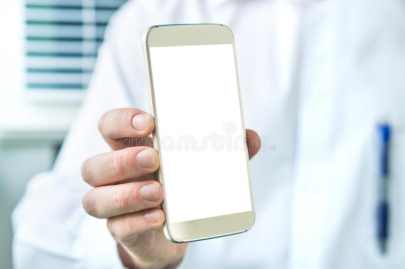 Doctor holding smartphone with empty blank white screen. Medical professional, physician, nurse or dentist showing mobile phone with copy space royalty free stock images