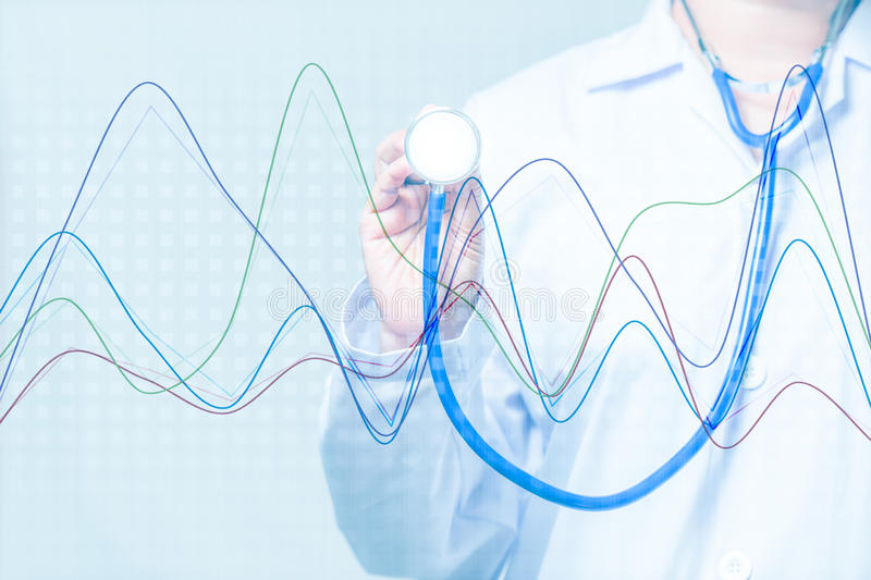 Doctor holding a stethoscope with graph on blue background. Doctor holding a stethoscope with graph on blue technology background stock photo