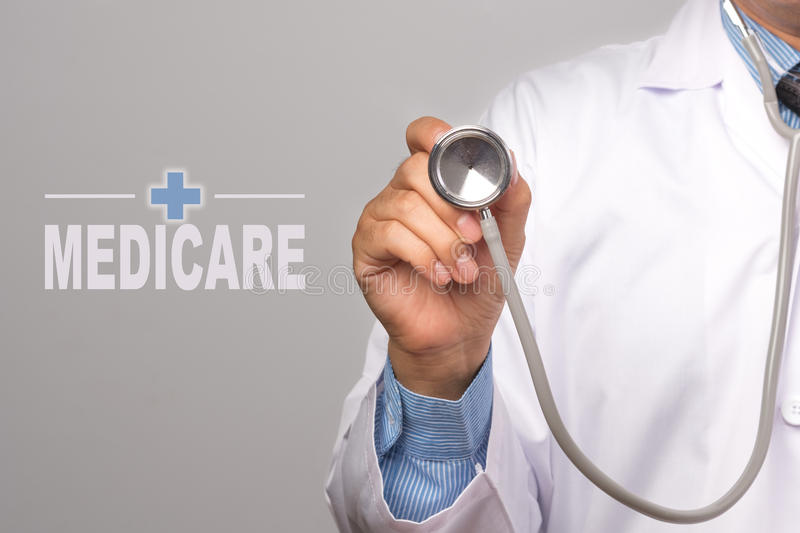 Doctor holding a stethoscope and word. `MEDICARE` on gray background. concept Healthy stock image