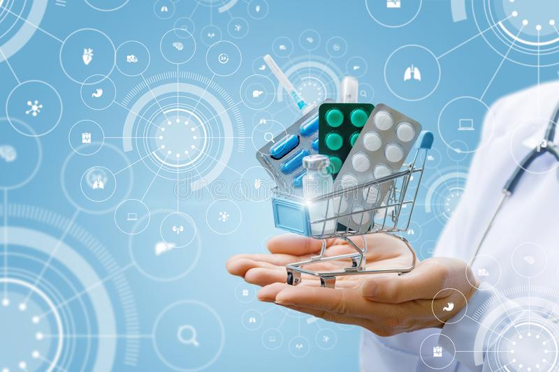 A doctor is holding a supermarket cart full of pills and drugs on her palms at the background of medical symbols digital system. The concept is the importance royalty free stock photo
