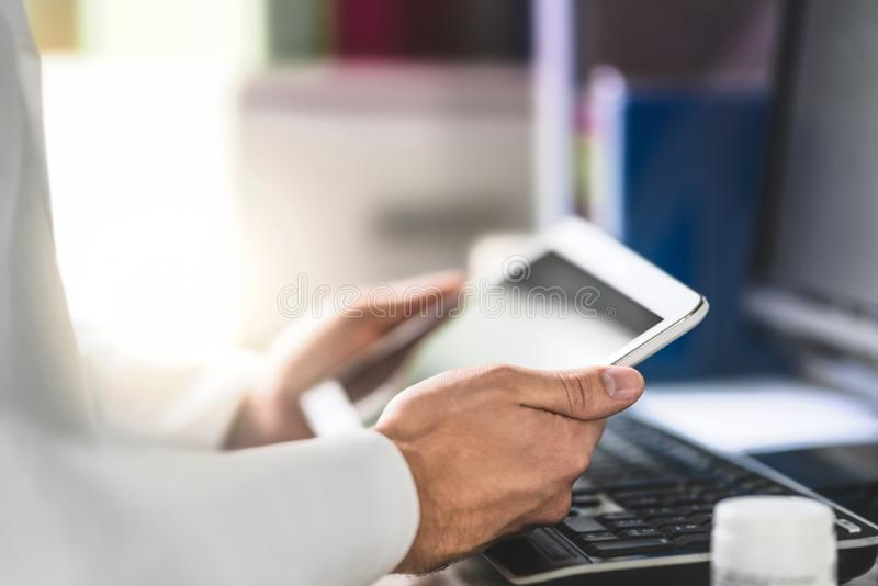 Doctor holding tablet in hand and reading medical record of patient. stock images