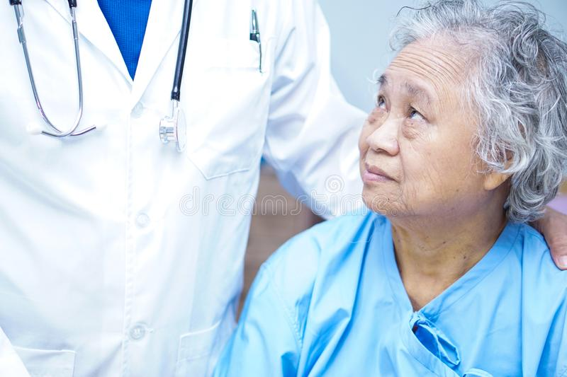 Doctor holding touching Asian senior or elderly old lady woman patient with love, care. Doctor holding touching hands Asian senior or elderly old lady woman royalty free stock image