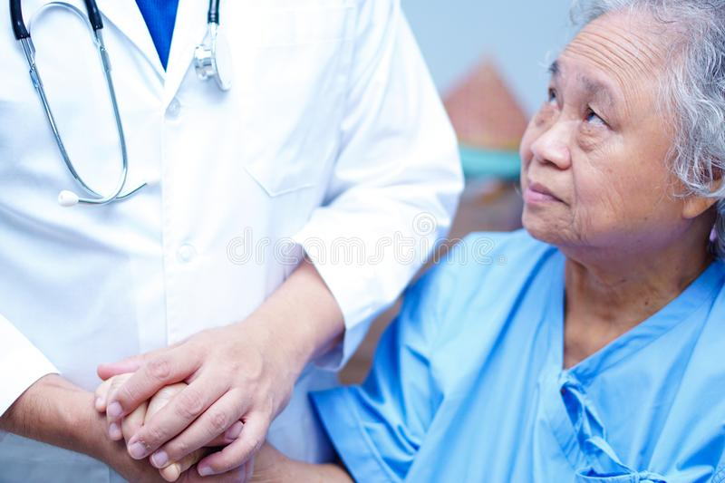 Doctor holding touching hands Asian senior or elderly old lady woman patient with love, care. Doctor holding touching hands Asian senior or elderly old lady stock images