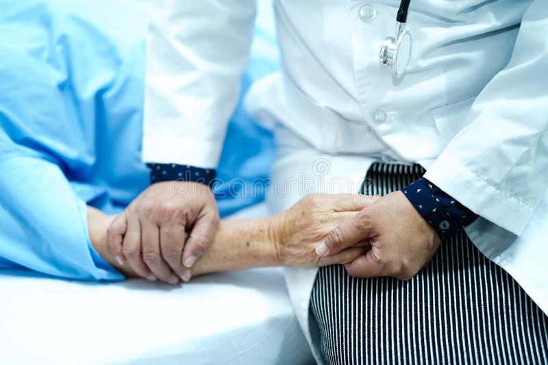 Doctor holding touching hands Asian senior or elderly old lady woman patient with love, care, helping, encourage and empathy. Doctor holding touching hands stock photography
