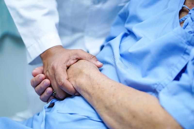 Doctor holding touching hands Asian senior or elderly old lady woman patient with love, care, helping, encourage and empathy. Doctor holding touching hands stock images