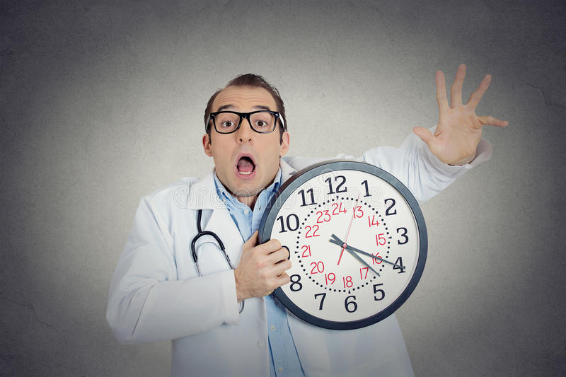 Doctor holding wall clock running out of time. Closeup portrait overwhelmed, busy, unhappy male health care professional, funny looking doctor guy holding wall stock photography
