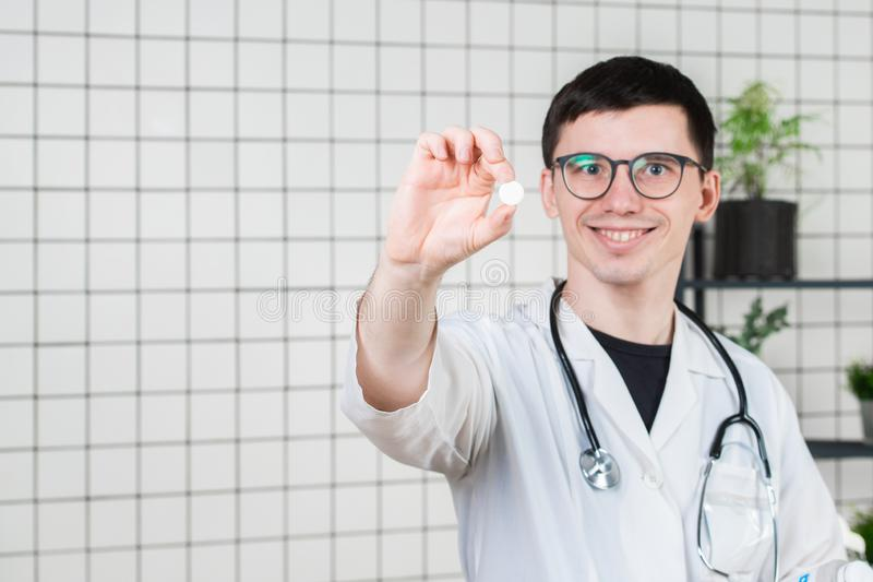 Doctor holding white pill, close-up. Concept of pharmacist, drugs, diet pill, antibiotics or vitamins royalty free stock photo