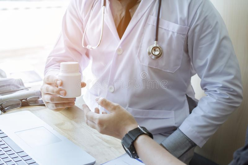 Doctor holding white pill. And patient counseling Should eat, morning, afternoon, evening, after eating. royalty free stock photo