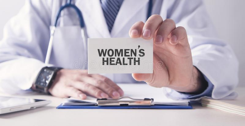 Doctor holding Women`s Health text on card. Medical concept royalty free stock photo