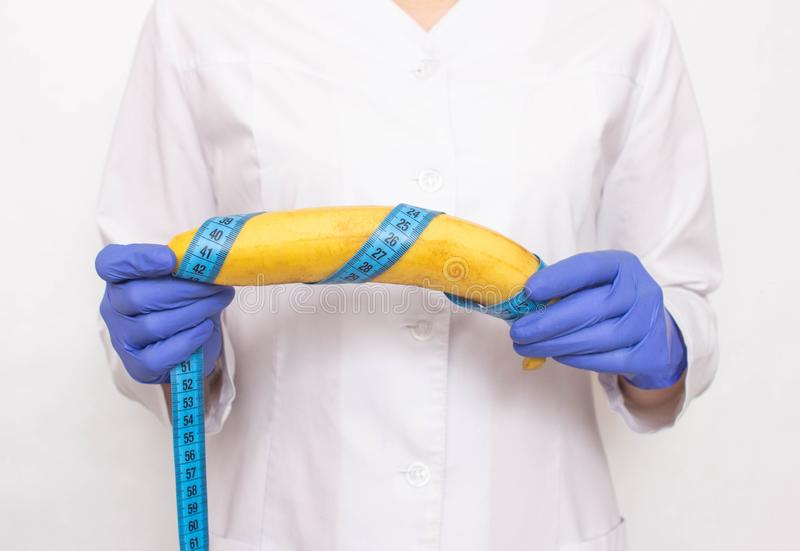 Doctor holds banana in hand with measuring tape. Concept of increasing male penis and operation, increase male organ. Doctor holds banana in hand with measuring royalty free stock photography
