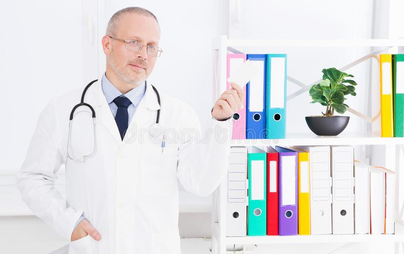 Doctor holds a business card in his office stock photos