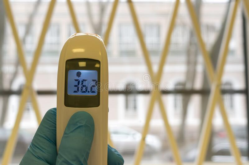 The doctor holds the infrared non-contact thermometer. The digital device displays the normal body temperature in degrees Celsius.  royalty free stock images